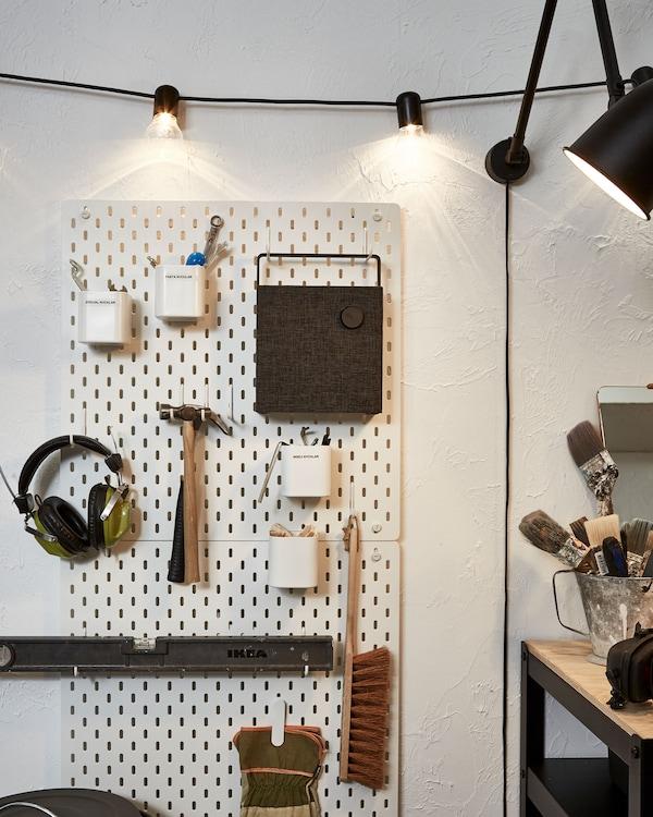 墙上装饰着钉板、灯串和灯具,钉板上存放着工具、耳机和蓝牙音箱。