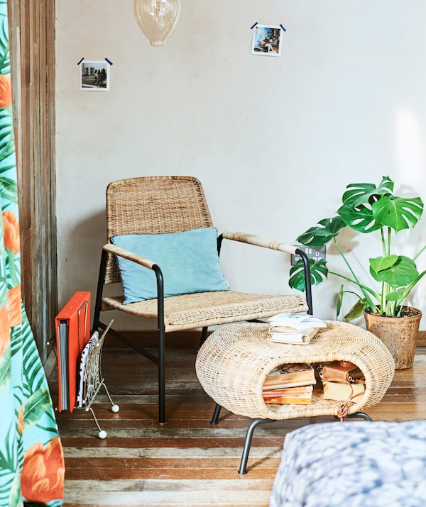 Rattan easy chair and footstool with storage space full of books in the corner of a room with decorative bulb hanging above.