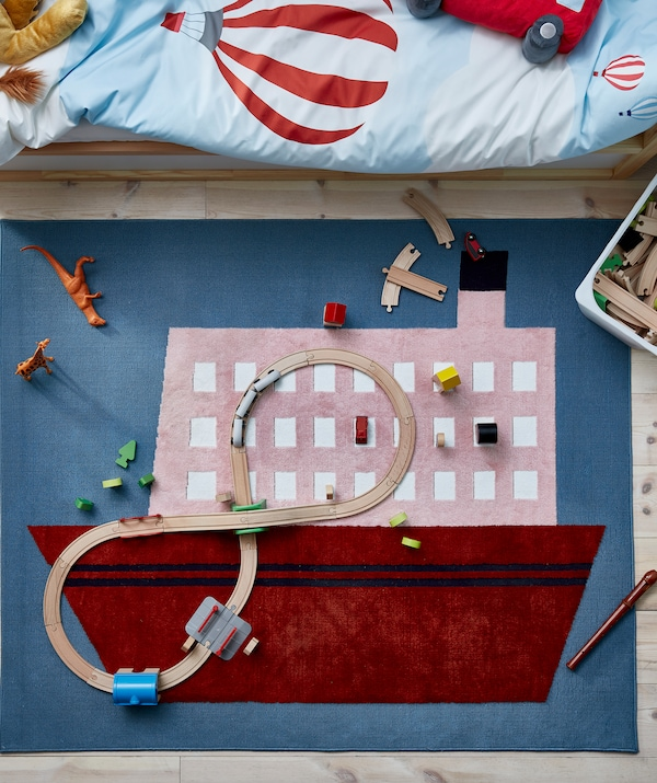 Rug with a boat motif, placed beneath a child's bed, scattered with wooden railroad parts and other toys.