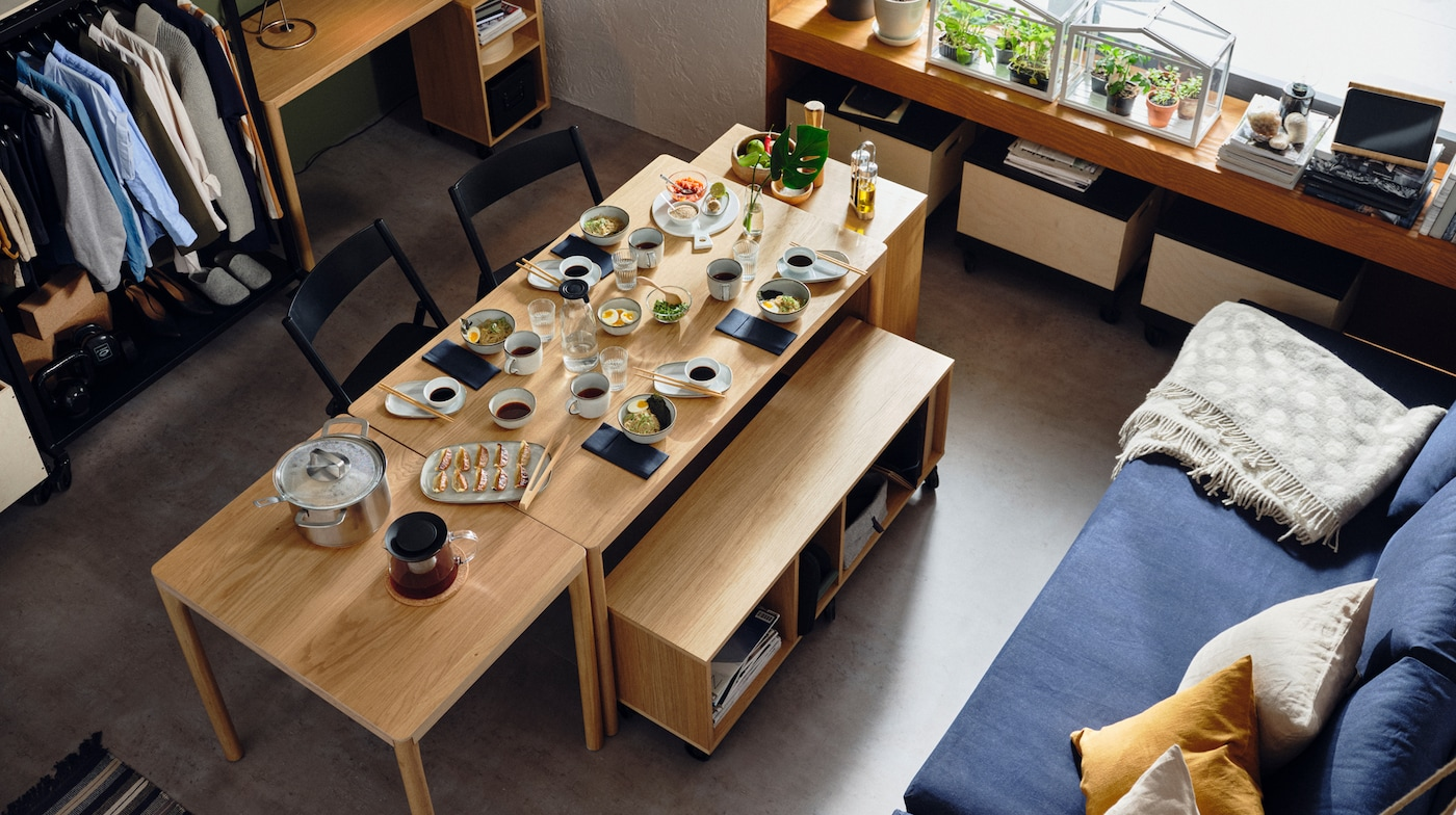 RÅVAROR 罗瓦露 桌子和储物单元组合成一个用餐区。桌子上摆满了用餐具装着的各种食物。