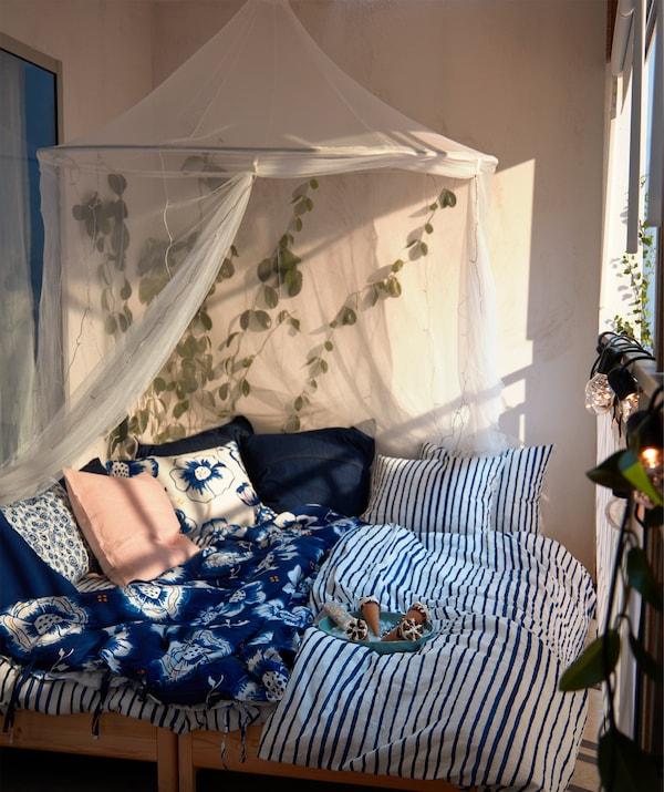 洒满阳光的阳台上摆放着一张双人床,上面铺有柔软的靠垫和蓝白相间的床上用品,床上还挂有蚊帐,四周则摆满植物。