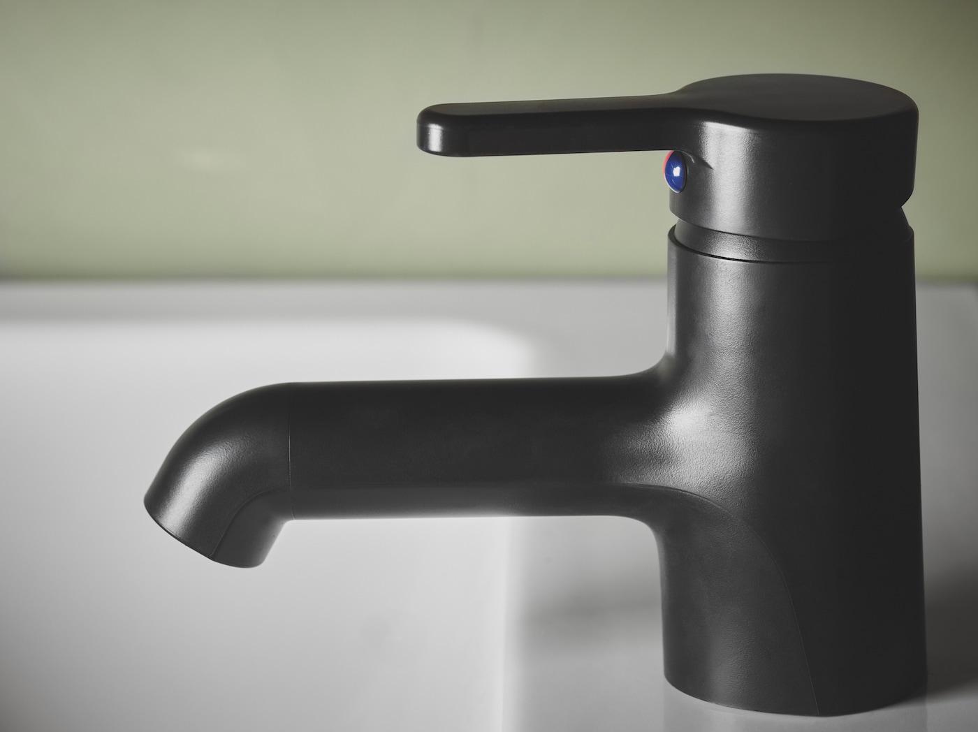 SALJEN 萨利恩 洗脸池水龙头风格简约,黑色塑料制成,搭配白色洗脸池使用。