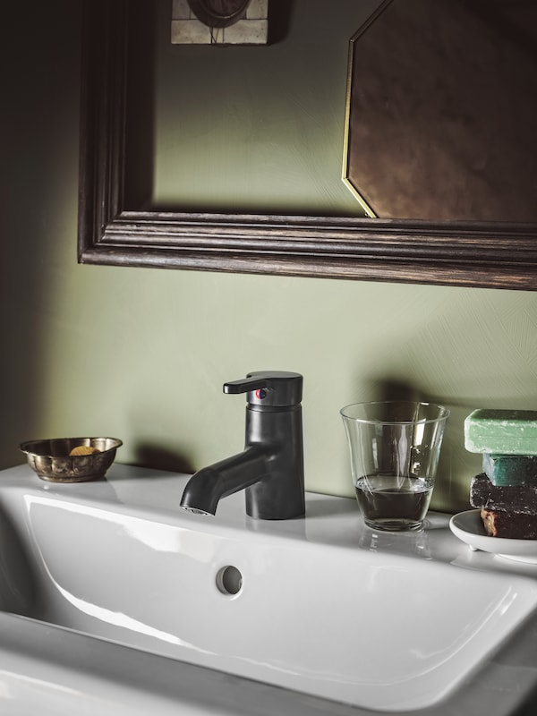 SALJEN wash-basin mixer tap made in black plastic placed by a white wash basin in a mint-green bathroom with a mirror.