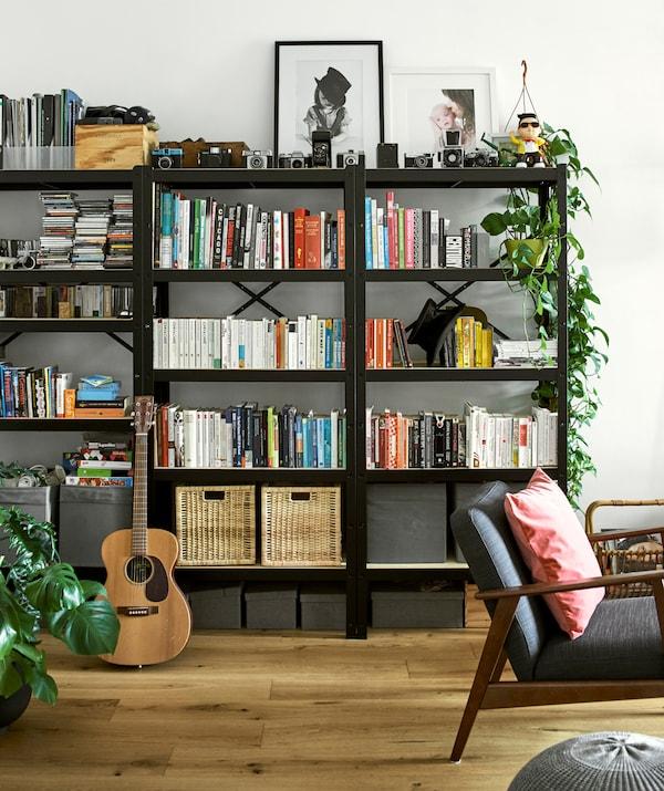 三个黑色书架上摆满了颜色协调的书本、柳条篮、带框照片、复古相机和植物。