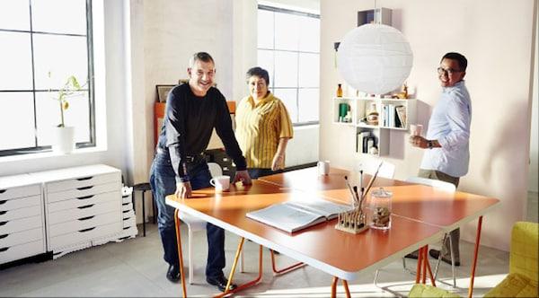 三名宜家员工同在一个房间中,里面摆着两张橙色书桌、椅子、一张白色抽屉柜和开放式壁式搁板。