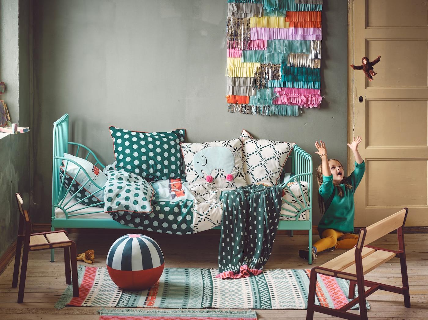 色彩斑斓的房间里摆放着 KÄPPHÄST 谢普海斯特 被套、地毯和软垫,一个孩子正把玩具猴子抛向空中。