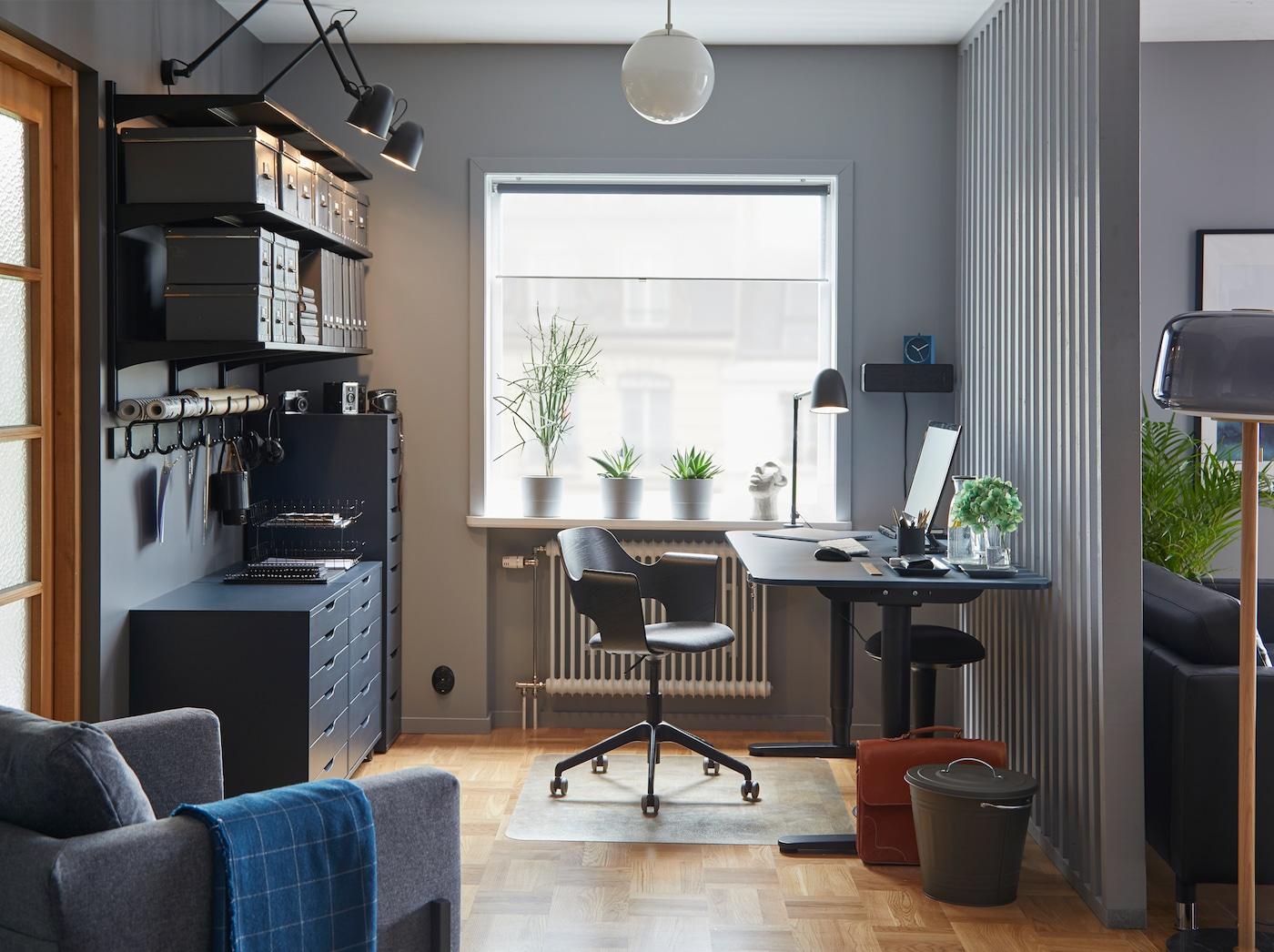 色彩协调的家庭办公室工作空间里配有 BEKANT 贝肯特 油毡蓝色/黑色坐/站两用式书桌、会议椅和储物件。