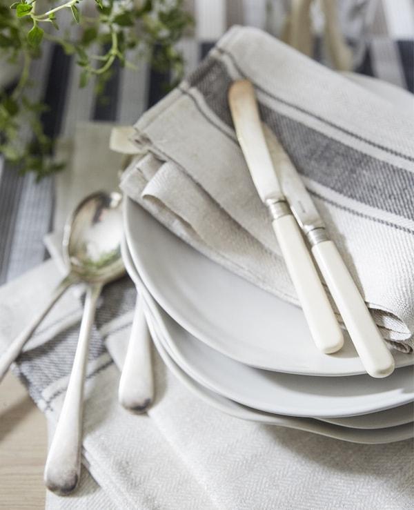 色调素净的棉质餐巾,以及摆放在一叠白色餐盘上的刀叉。