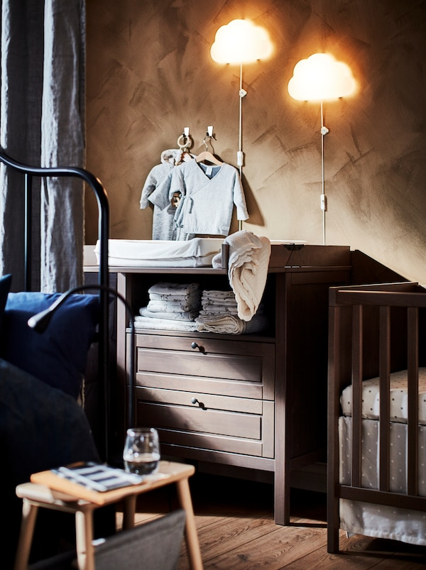 Section of a bedroom, half hidden behind a room-dividing curtain, with a baby's cot and a SUNDVIK changing table.