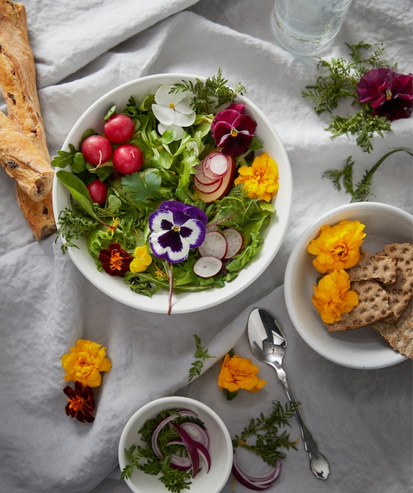 Section of a table set with a white, creased cloth, different-size bowl filled with bread, homegrown greens, and flowers.