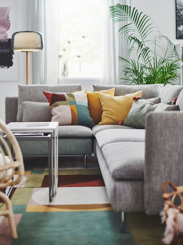 Section of living room with a grey SÖDERHAMN corner sofa, a host of colourful cushions on it and standing on a colourful rug.