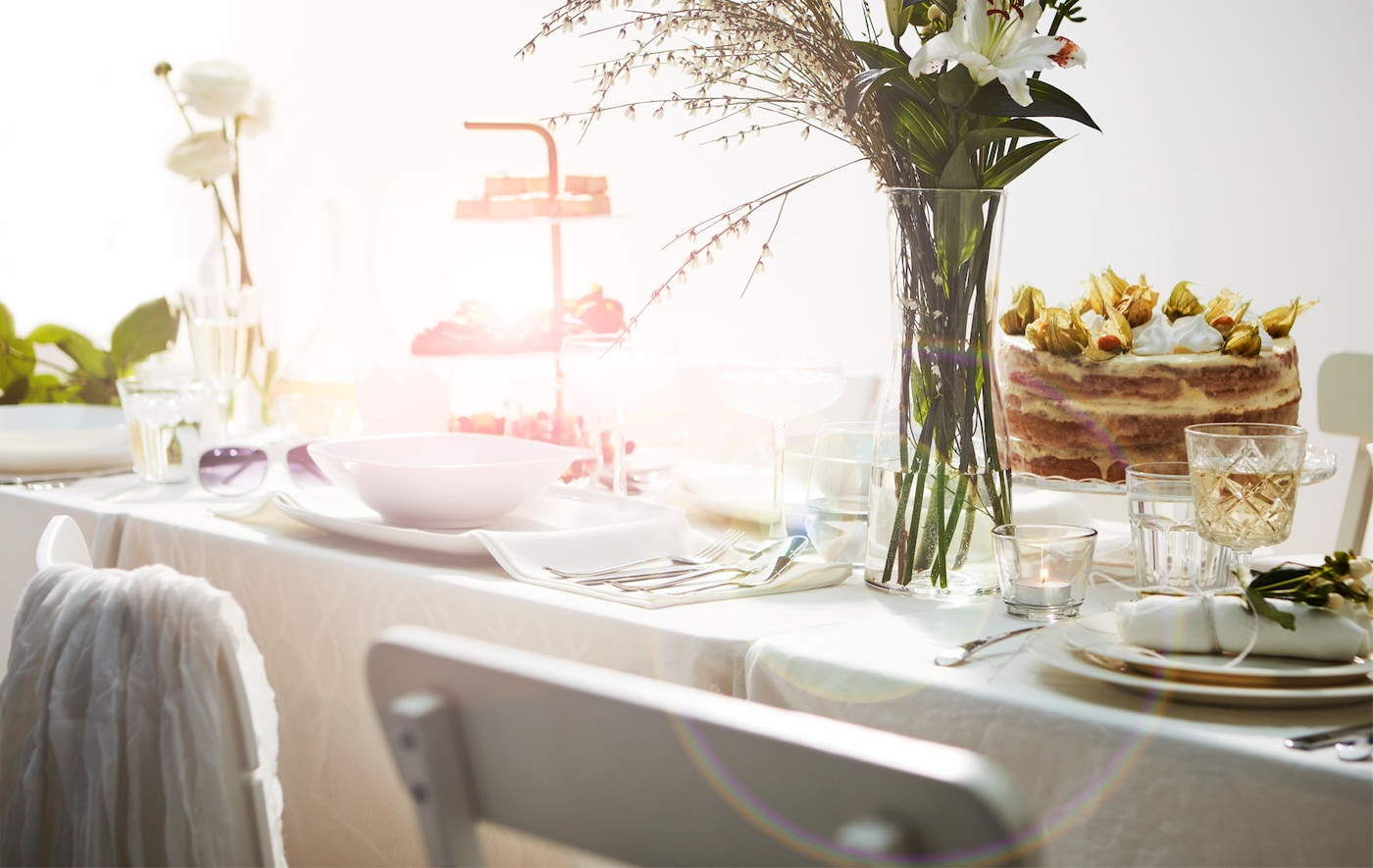 Section of long table set in a romantic, lavish way with white furniture, cloth and tableware; cake, cookie tray and flowers.