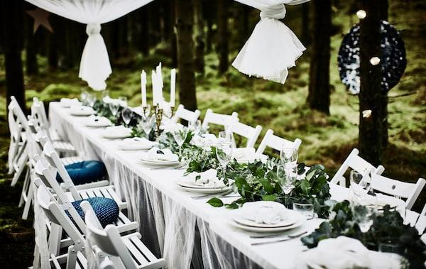 森林婚礼的餐桌桌面为白色,桌上铺有花边窗帘桌布,周围放着白色的折叠椅,桌上摆放着白色的餐具和绿色植物打造的长桌布中心饰物