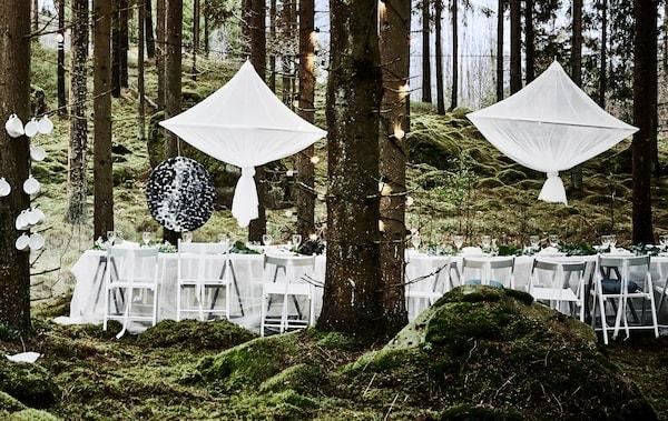 森林婚礼派对餐桌布局,摆着白色的椅子、蕾丝窗帘桌布,餐桌上方悬挂着巨大的枝形吊灯风格中心装饰物
