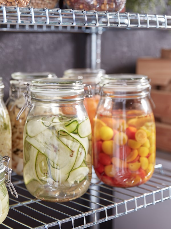 Several KORKEN glass jars with lids filled with colourful pickled vegetables of different kinds, standing on metal shelves.