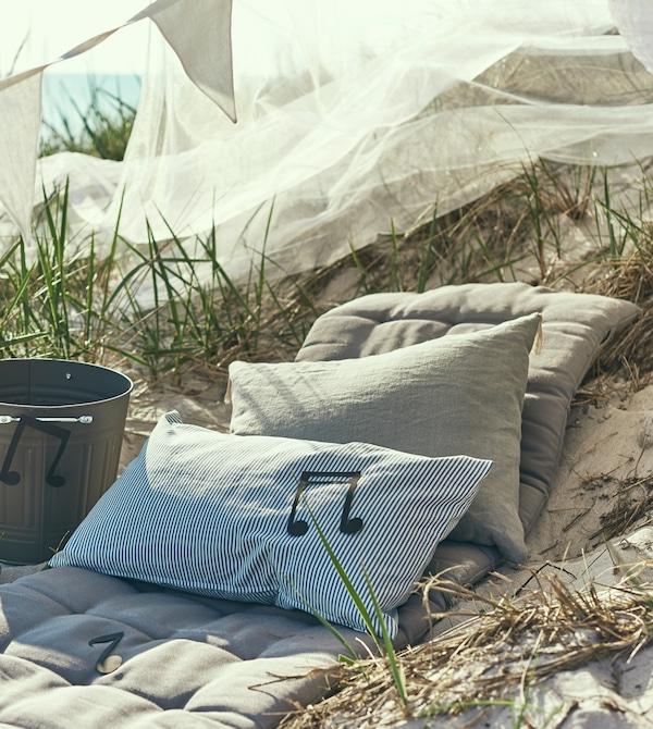 沙滩上有一些靠垫,旁边是用桶DIY的一个扬声器。