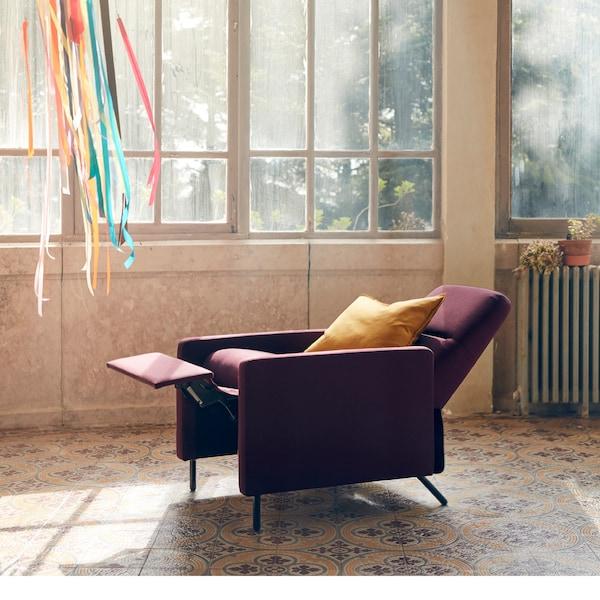 深红色的 GISTAD 基斯塔 躺椅简洁雅致,倾斜度调至平躺,摆放在房间中央。