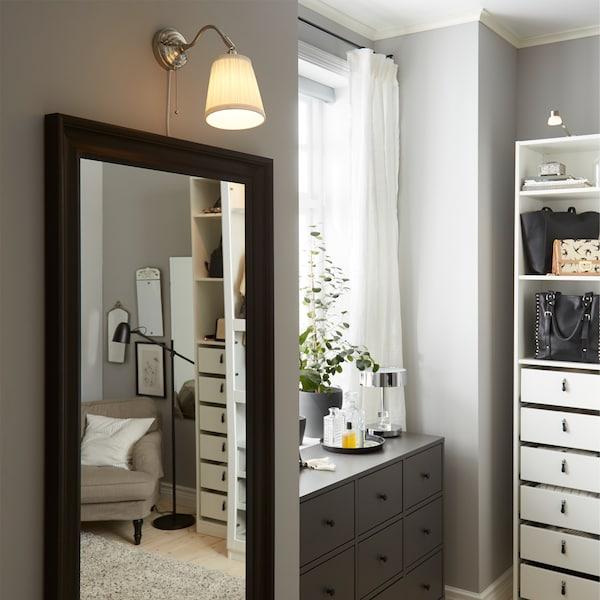 深灰色抽屉柜、黑褐色镜子和镀镍/白色壁灯。