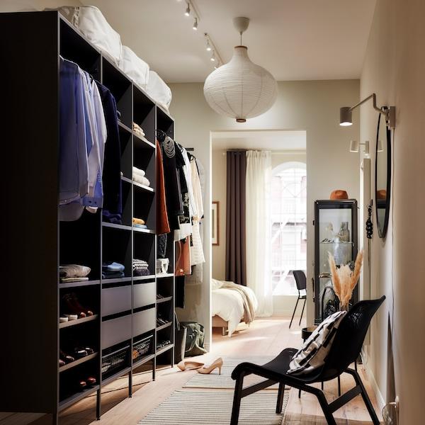 深灰色的大型开放式衣柜解决方案由搁板、挂衣杆和四个抽屉组成。搁板上放着折叠好的衣服,挂衣杆上挂着衣服。