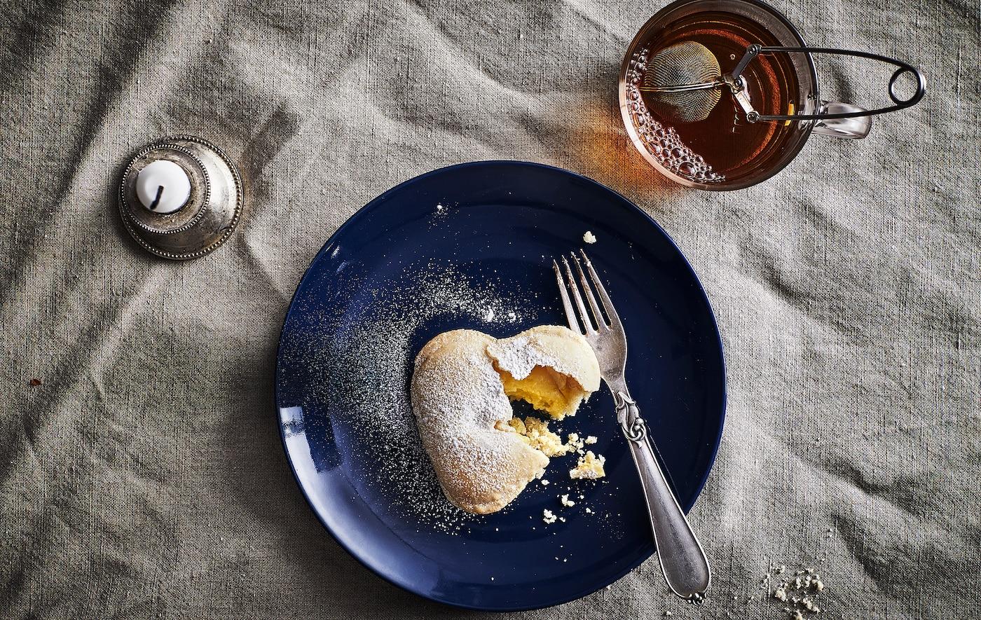 深蓝色的碟子里摆放着香草心型饼干和叉子,旁边还有一杯茶和一根蜡烛。