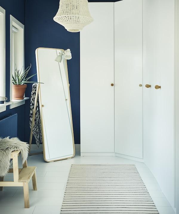 深蓝色的房间内有一面白色衣柜墙和一面镜子。