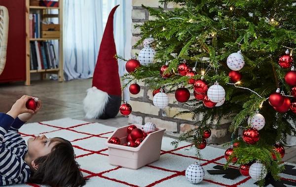 圣诞树上挂满了装饰品,旁边的小男孩脸朝天躺在地毯上,观察着一个装饰品。