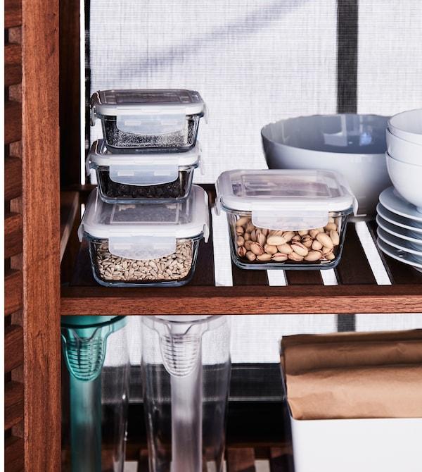 食品储物盒和餐具存放在封闭式的木制储物柜里。