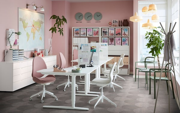 饰有粉色墙壁的办公空间内摆放着 BEKANT 贝肯特 白色坐/站两用办公桌和 HATTEFJÄLL 哈德夫耶尔 转椅。