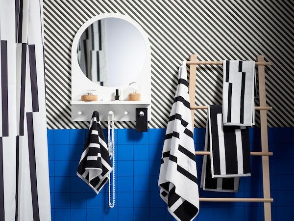 饰有条纹的蓝色浴室,里面配有 SALTRÖD 萨罗德 镜子带搁板和挂钩和 VILTO 维尔托 毛巾架,架子上挂着条纹毛巾。