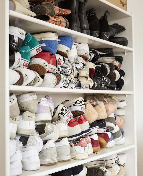 Shoes stacked on a bookcase.