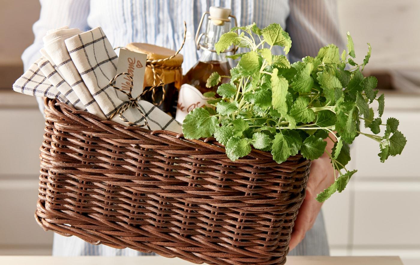 手里拿着一个 GABBIG 伽比 篮筐,里面装着带有装饰带的厨房用巾、玻璃罐装的自制蜜饯和新鲜香草。