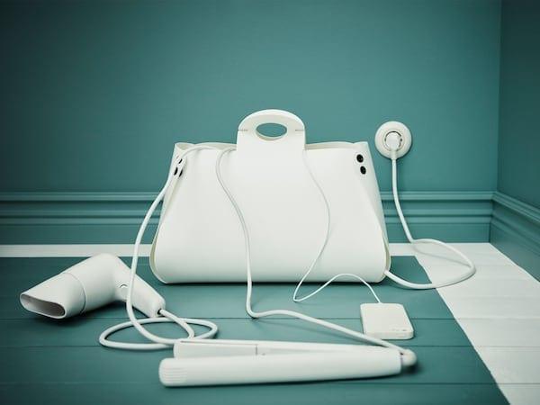 手提包形状的白色电线管理袋,一起展示的还有伸出来的电线。