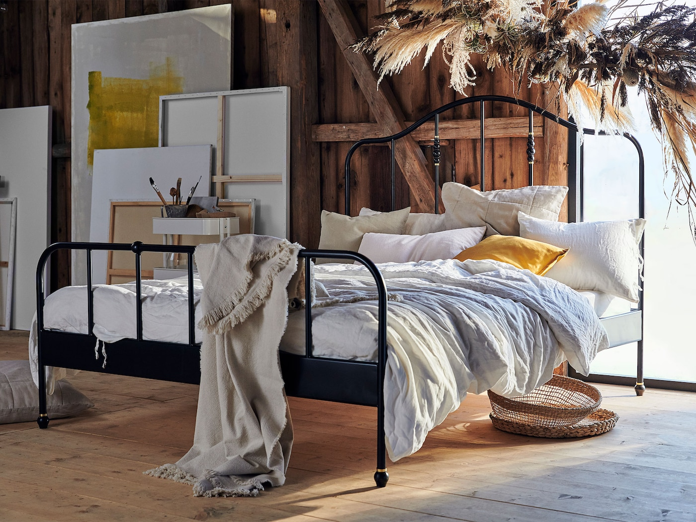 Shown in a rustic loft, the curvy, airy SAGSTUA bed frame in black-coated steel has a tall headboard and easy-to-match look.