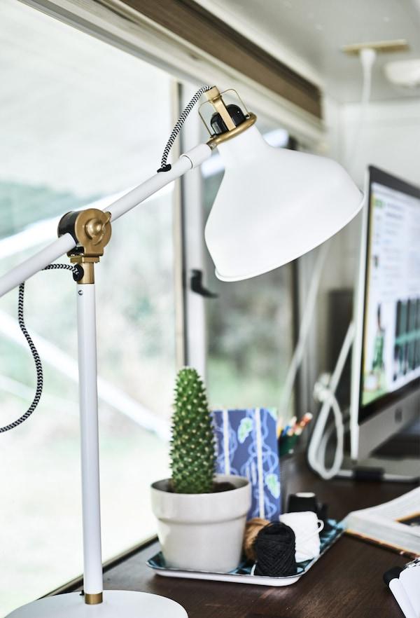 书桌上摆放着灯具,背景中有一株仙人掌和一些文具。