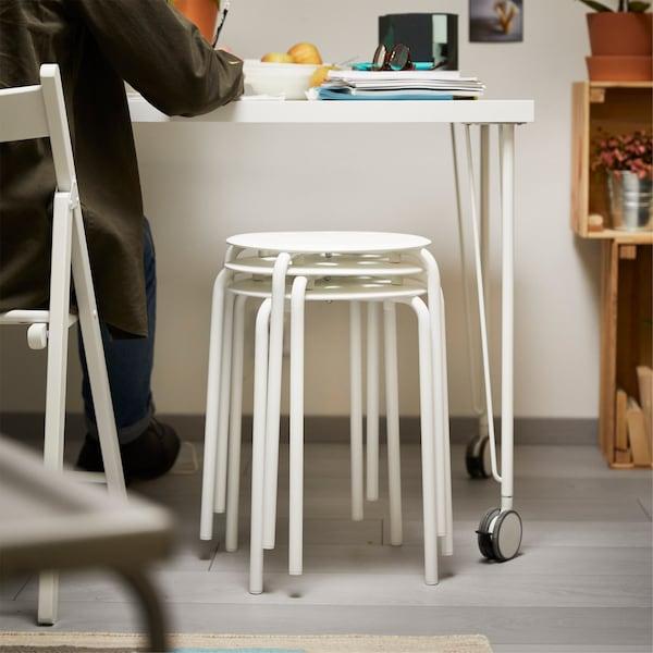 书桌下面堆叠摆放着一些凳子。
