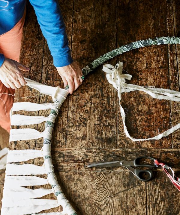 双手将自然色布条绑在用蓝色和绿色布料缠绕的呼啦圈上,以打造流苏效果。