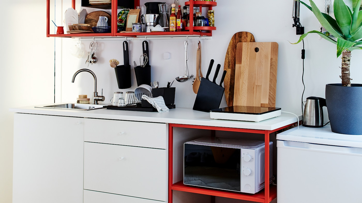 Small kitchen in red/white with a portable induction hob, wooden chopping boards, and a black dish drainer.
