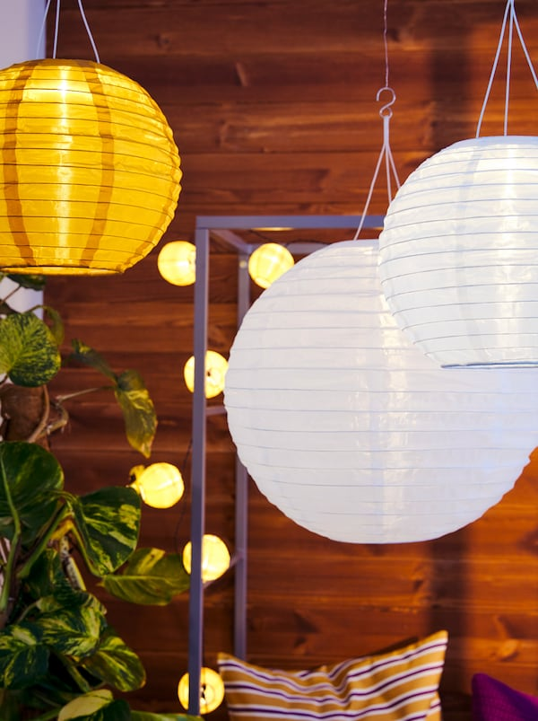 SOLVINDEN solar-powered lamps hang by a SVANÖ arbor bench on a balcony. The bench is decorated with a lighting chain.