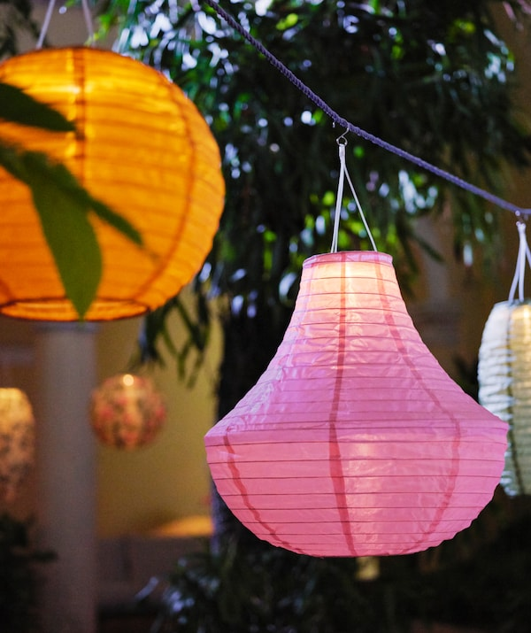 SOLVINDEN solar-powered pendant lamps in different shapes and colours hang at intervals in a lush garden.
