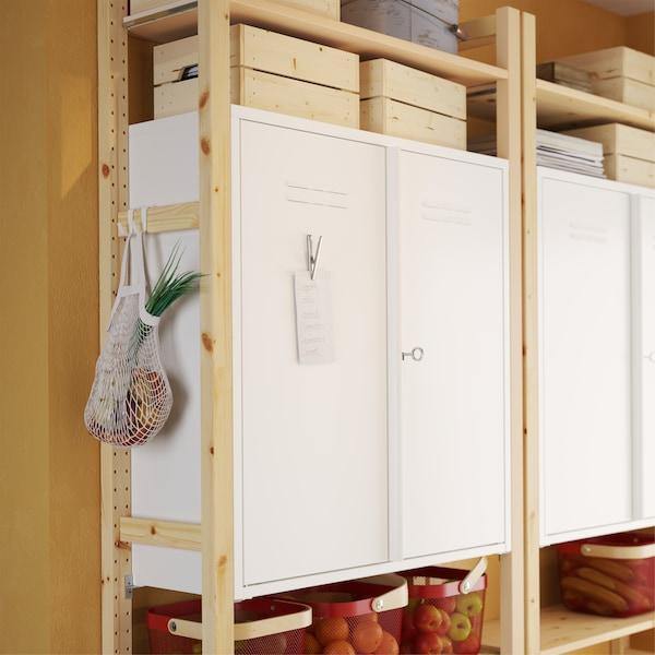松木搁板组件上是 IVAR 伊娃 白色金属储物柜,储物柜的金属柜门上有一个夹着便条的金属夹。