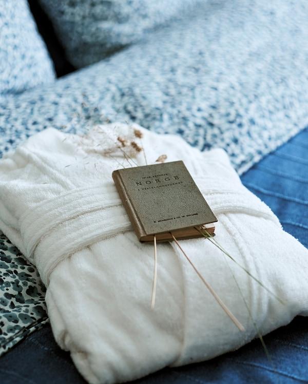松软的白色浴袍折叠放在罩有蓝色床罩的床上,还有一本古香古色,关于挪威的书摆放在草茎旁。