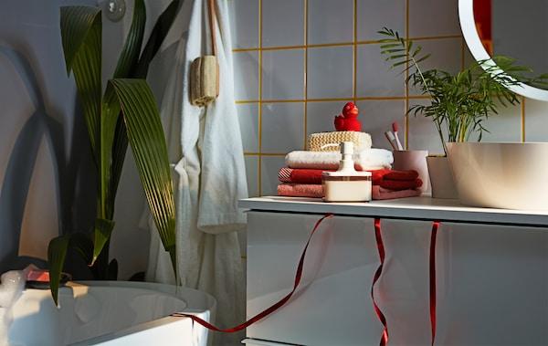 松散的包装丝带掉落在浴室内紧闭的 GODMORGON 古德莫 洗脸池柜顶层抽屉之外,提示这里可能藏有礼物。
