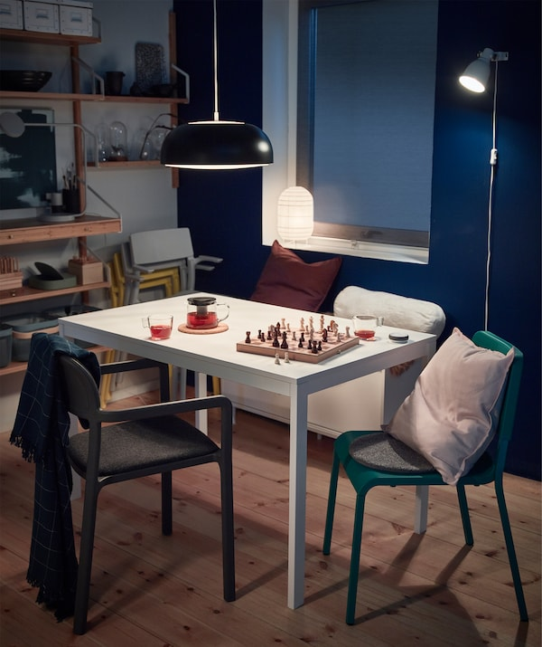 Spend cosy nights around the table. Bring out soft IKEA GURLI cushions and VÅRKRAGE polyester blankets from a white MACKAPÄR storage bench. It has sliding doors for storage. Adjustable and flexible lighting like HEKTAR puts focus on the table.