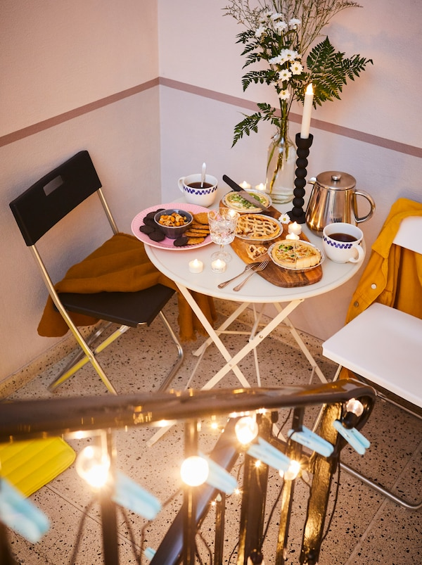 Stairwell platform with GUNDE chairs and a small table set with food on a FASCINERA chopping board, flowers and coffee.