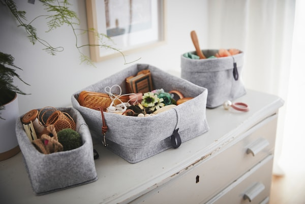 Standing on an old, worn chest of drawers is a set of RAGGISAR textile baskets, filled with trinkets and clutter.