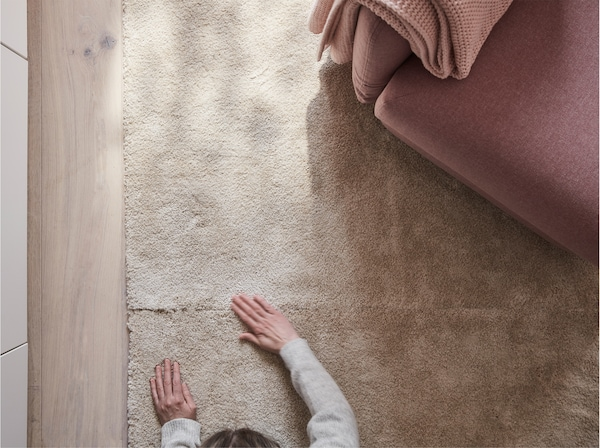 STOENSE low pile rug in off-white, seen from above in a living room, with a person feeling the rug's soft, dense surface.