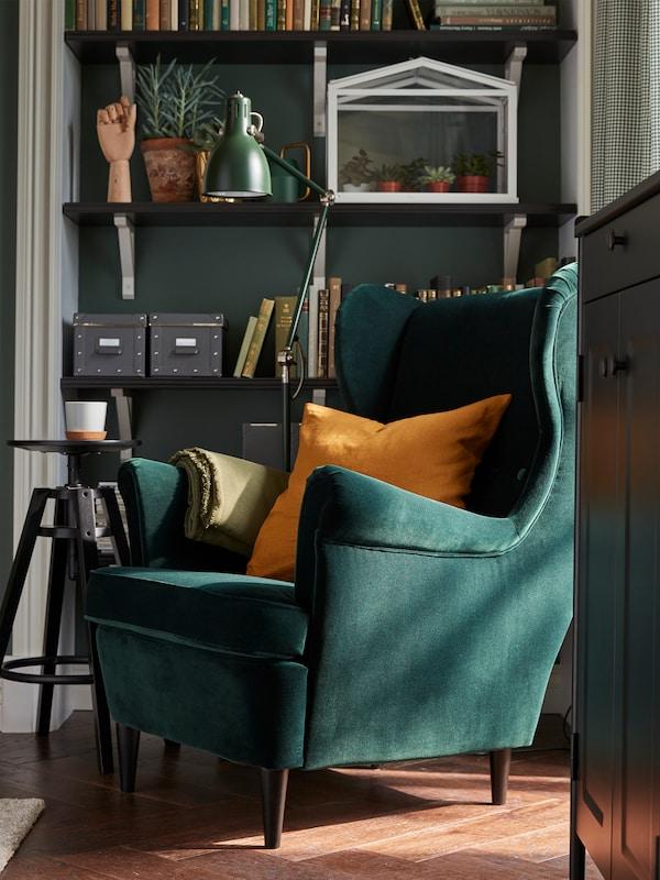 STRANDMON 斯佳蒙 深绿色扶手椅和黄褐色靠垫、倾斜的灯具和摆放着书本、植物的搁板。