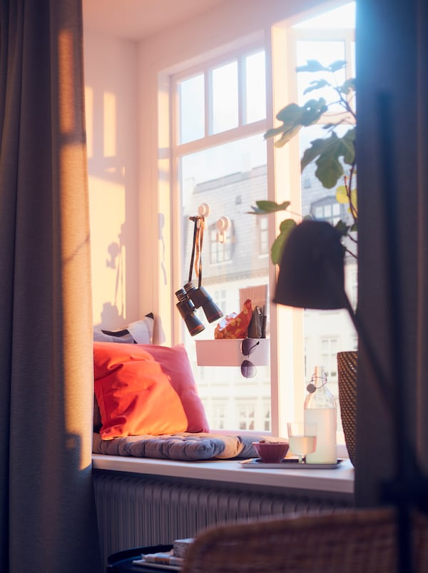 Sunlit window with a cityscape backdrop. On the sill a VIPPÄRT chair cushion, a tray of refreshments, and a large plant.