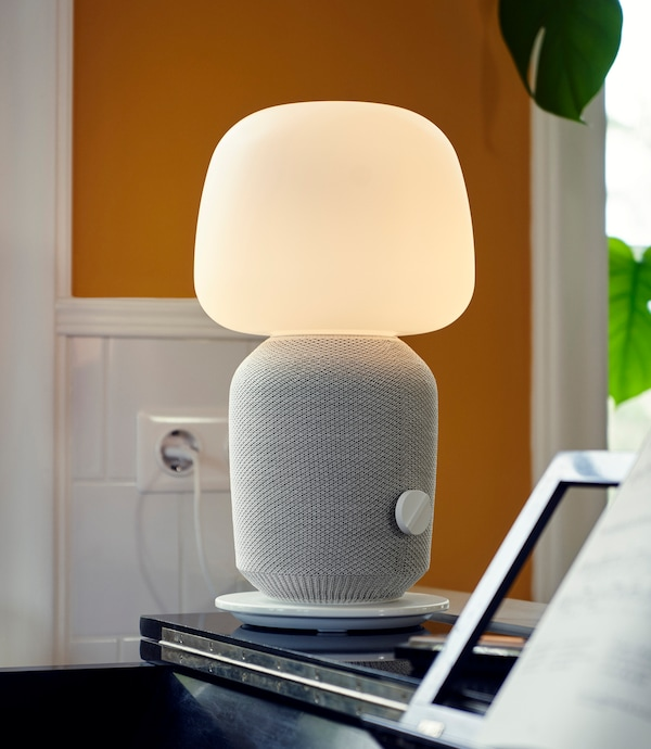 SYMFONISK WiFi speaker lamp, placed on a piano.