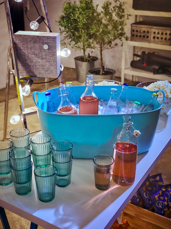 Table with stacked KALLNA glasses by a TISKEN laundry basket filled with ice and capped drinks, including KORKEN glass bottles.